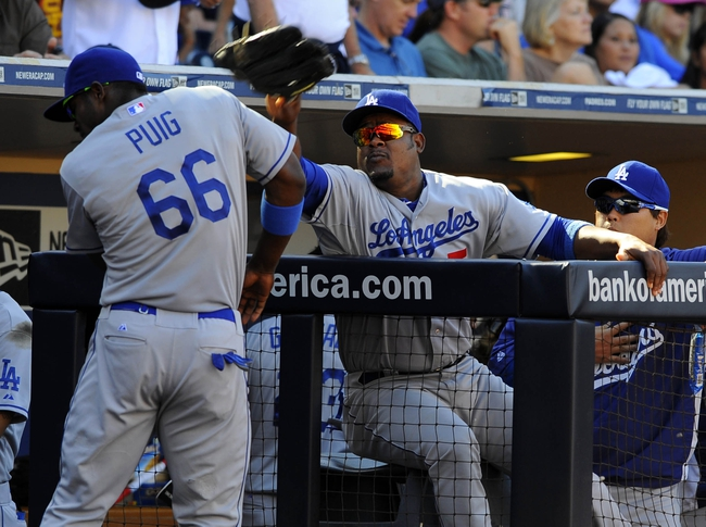 Sep 22, 2013; San Diego, CA, USA; Los Angeles Dodgers third base Juan Uribe (5) throws a glove at right fielder Yasiel Puig (66) during the eighth inning against the San Diego Padres at Petco Park. Mandatory Credit: Christopher Hanewinckel-USA TODAY Sports