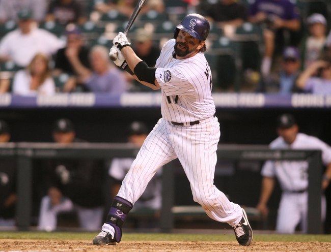 Sep 22, 2013; Denver, CO, USA; Colorado Rockies first baseman Todd Helton (17) hits an RBI single during the ninth inning against the Arizona Diamondbacks at Coors Field. The Diamondbacks won 13-9.  Mandatory Credit: Chris Humphreys-USA TODAY Sports