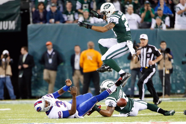 Sep 22, 2013; East Rutherford, NJ, USA;  Buffalo Bills quarterback EJ Manuel (3) is tackled by New York Jets strong safety Dawan Landry (26) as cornerback Dee Milliner (27) leaps over during the fourth quarter at MetLife Stadium. Mandatory Credit: Anthony Gruppuso-USA TODAY Sports