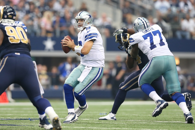 Sep 22, 2013; Arlington, TX, USA; Dallas Cowboys quarterback Tony Romo (9) scrambles in the fourth quarter against the St. Louis Rams at AT&T Stadium. The Dallas Cowboys beat St. Louis Rams 31-7. Mandatory Credit: Matthew Emmons-USA TODAY Sports