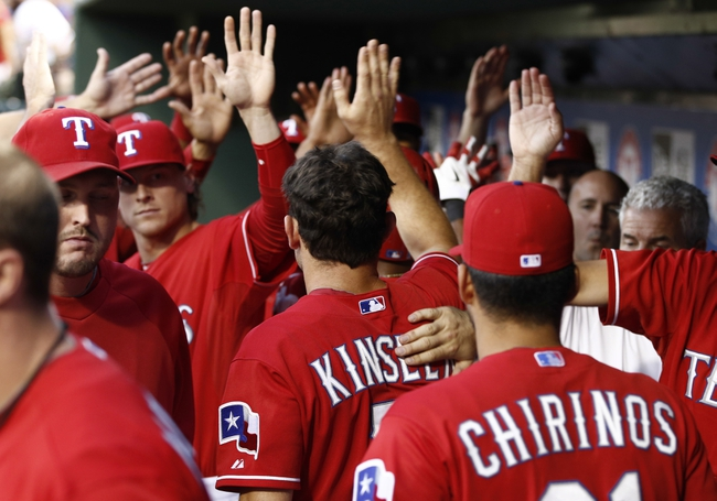 Sep 23, 2013; Arlington, TX, USA; Texas Rangers teammates congratulate second baseman Ian Kinsler (5) in the dugout after scoring a run against the Houston Astros during the first inning of a baseball game at Rangers Ballpark in Arlington. Mandatory Credit: Jim Cowsert-USA TODAY Sports