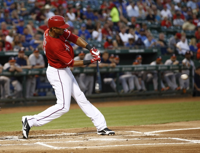 Sep 23, 2013; Arlington, TX, USA; Texas Rangers right fielder Alex Rios (51) hits a two run RBI double against the Houston Astros during the first inning of a baseball game at Rangers Ballpark in Arlington. Mandatory Credit: Jim Cowsert-USA TODAY Sports