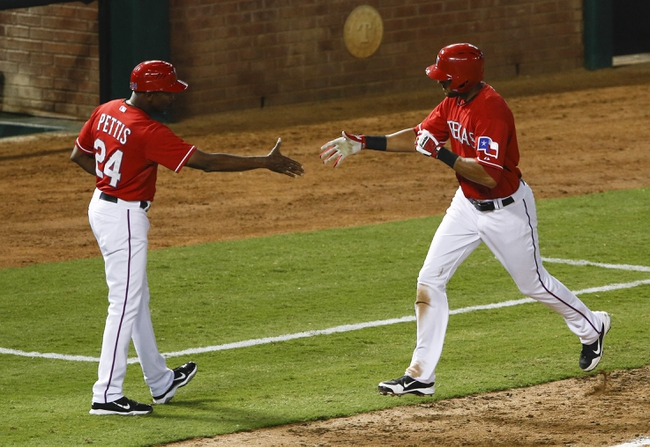 Sep 23, 2013; Arlington, TX, USA; Texas Rangers right fielder Alex Rios (right) is congratulated by third base coach Gary Pettis (24) after his solo home run against the Houston Astros during the fourth inning of a baseball game at Rangers Ballpark in Arlington. Mandatory Credit: Jim Cowsert-USA TODAY Sports