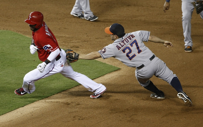 Sep 23, 2013; Arlington, TX, USA; Texas Rangers shortstop Elvis Andrus (1) is chased down and tagged out by Houston Astros second baseman Jose Altuve (27) after attempting to stretch a single into a double during the fourth inning of a baseball game at Rangers Ballpark in Arlington. Mandatory Credit: Jim Cowsert-USA TODAY Sports