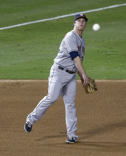 Sep 23, 2013; Arlington, TX, USA; Houston Astros third baseman Matt Dominguez (30) makes a throwing error to first base on a hit by Texas Rangers second baseman Ian Kinsler (not shown) during the fourth inning of a baseball game at Rangers Ballpark in Arlington. Mandatory Credit: Jim Cowsert-USA TODAY Sports