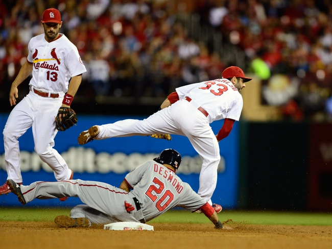 Sep 23, 2013; St. Louis, MO, USA; St. Louis Cardinals shortstop Daniel Descalso (33) leaps over Washington Nationals shortstop Ian Desmond (20) as he turns a double play during the fourth inning at Busch Stadium. Mandatory Credit: Jeff Curry-USA TODAY Sports
