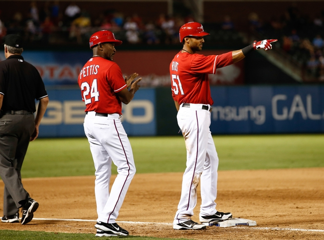 Sep 23, 2013; Arlington, TX, USA; Texas Rangers right fielder Alex Rios (51) points to the Rangers dugout after hitting the cycle as third base coach Gary Pettis (24) looks on against the Houston Astros during the sixth inning of a baseball game at Rangers Ballpark in Arlington. Rios is the seventh in Rangers history to hit for the cycle. Mandatory Credit: Jim Cowsert-USA TODAY Sports