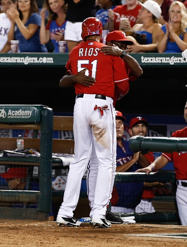 Sep 23, 2013; Arlington, TX, USA; Texas Rangers right fielder Alex Rios (51) is congratulated and hugged by manager Ron Washington (38) after scoring against the Houston Astros during the sixth inning of a baseball game at Rangers Ballpark in Arlington. Rios completed hitting for the cycle before scoring. Mandatory Credit: Jim Cowsert-USA TODAY Sports