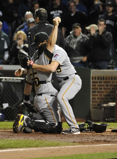 Sep 23, 2013; Chicago, IL, USA; Pittsburgh Pirates catcher Russell Martin (55) is greeted by Pittsburgh Pirates relief pitcher Jason Grilli (39) after tagging out Chicago Cubs right fielder Nate Schierholtz (not pictured) at home plate to end the game at Wrigley Field. The Pittsburgh Pirates defeated the Chicago Cubs 2-1.Mandatory Credit: David Banks-USA TODAY Sports