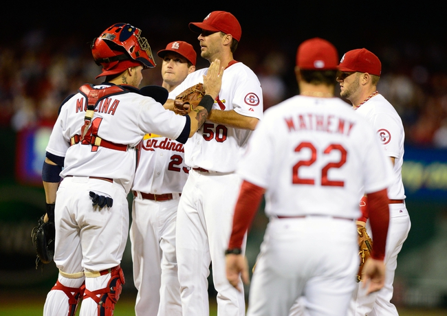 Sep 23, 2013; St. Louis, MO, USA; St. Louis Cardinals starting pitcher Adam Wainwright (50) talks with catcher Yadier Molina (4) as manager Mike Matheny (22) walks out to remove him from the game during the eighth inning against the Washington Nationals at Busch Stadium. St. Louis defeated Washington 4-3. Mandatory Credit: Jeff Curry-USA TODAY Sports