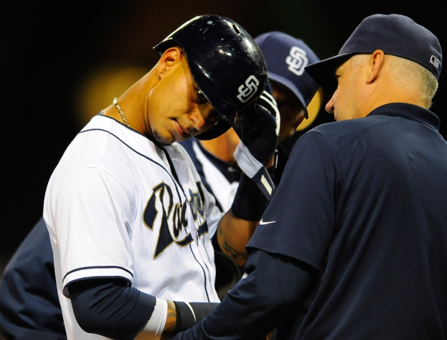 Sep 23, 2013; San Diego, CA, USA; San Diego Padres shortstop Ronny Cedeno (3) is looked at by team trainer Todd Hutcheson (right) and manager Bud Black (back) after being hit in the head by a pitch during the seventh inning against the Arizona Diamondbacks at Petco Park. Mandatory Credit: Christopher Hanewinckel-USA TODAY Sports
