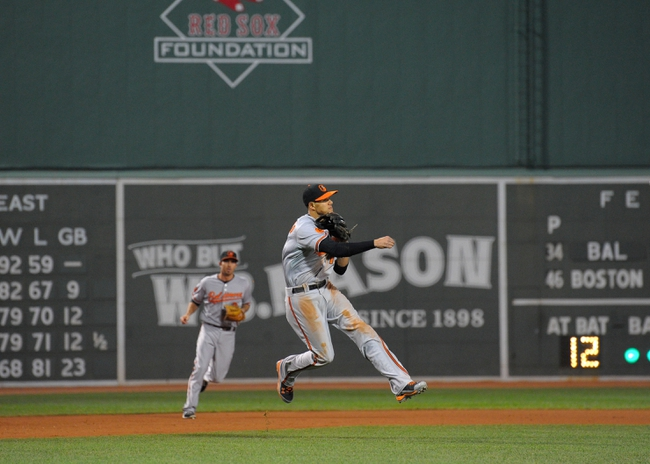 Sep 17, 2013; Boston, MA, USA; Baltimore Orioles third baseman Manny Machado (13) makes a throw to first base for an out during the first inning against the Boston Red Sox at Fenway Park. Mandatory Credit: Bob DeChiara-USA TODAY Sports