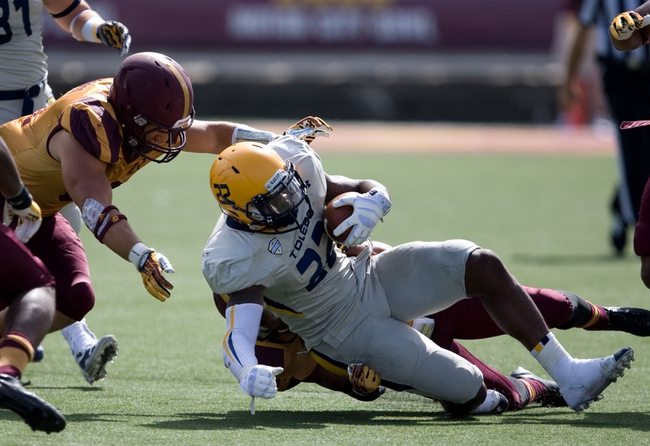 Sep 21, 2013; Mount Pleasant, MI, USA; Toledo Rockets running back David Fluellen (22) gets tackled during the second quarter against the Central Michigan Chippewas at Kelly/Shorts Stadium. Rockets beat the Chippewas 38-17. Mandatory Credit: Raj Mehta-USA TODAY Sports