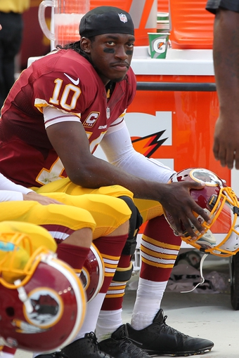 Sep 22, 2013; Landover, MD, USA; Washington Redskins quarterback Robert Griffin III (10) watches from the sidelines against the Detroit Lions in the fourth quarter at FedEx Field. The Lions won 27-20. Mandatory Credit: Geoff Burke-USA TODAY Sports