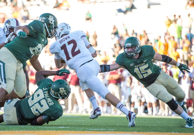 Sep 21, 2013; Waco, TX, USA; Louisiana Monroe Warhawks quarterback Brayle Brown (12) is tackled by Baylor Bears defensive end Jamal Palmer (92) and linebacker Brody Trahan (15) during the game at Floyd Casey Stadium. The Bears defeated the Warhawks 70-7. Mandatory Credit: Jerome Miron-USA TODAY Sports