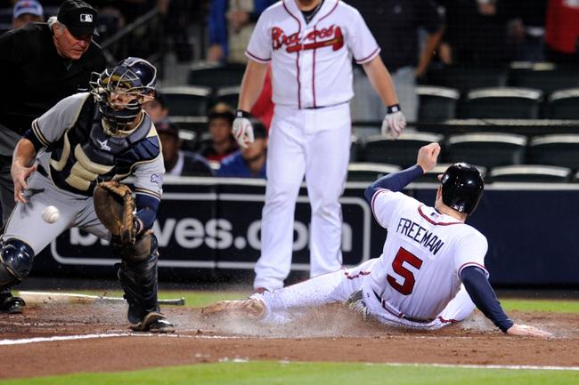 Sep 24, 2013; Atlanta, GA, USA; Atlanta Braves first baseman Freddie Freeman (5) scores behind Milwaukee Brewers catcher Jonathan Lucroy (20) during the fourth inning at Turner Field. Mandatory Credit: Dale Zanine-USA TODAY Sports