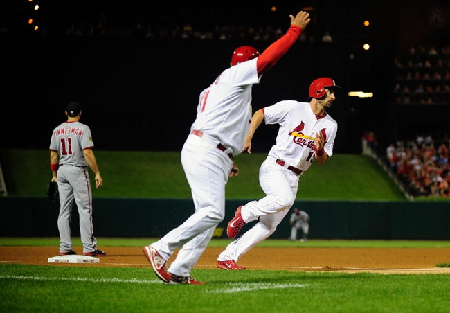 Sep 24, 2013; St. Louis, MO, USA; St. Louis Cardinals second baseman Matt Carpenter (13) is waved home by third base coach Jose Oquendo (11) during the third inning against the Washington Nationals at Busch Stadium. Mandatory Credit: Jeff Curry-USA TODAY Sports