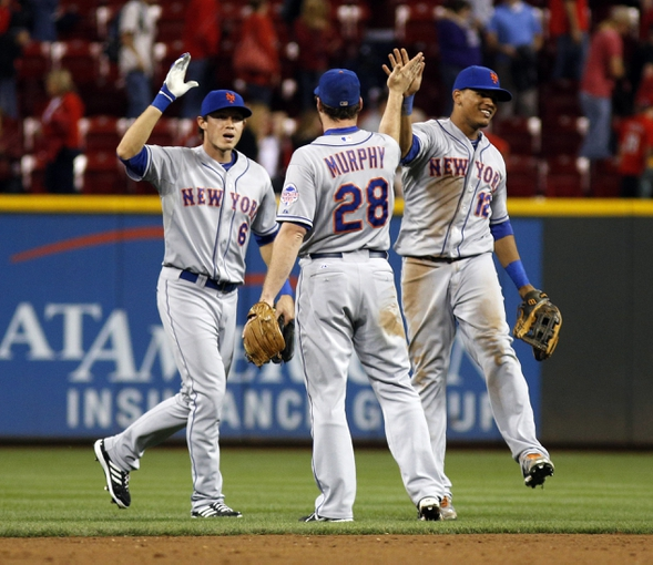 Sep 24, 2013; Cincinnati, OH, USA; New York Mets second baseman Daniel Murphy (28) is congratulated by right fielder Matt den Dekker (6) and center fielder Juan Lagares (12) after the Mets beat the Cincinnati Reds 4-2 at Great American Ball Park. Mandatory Credit: David Kohl-USA TODAY Sports