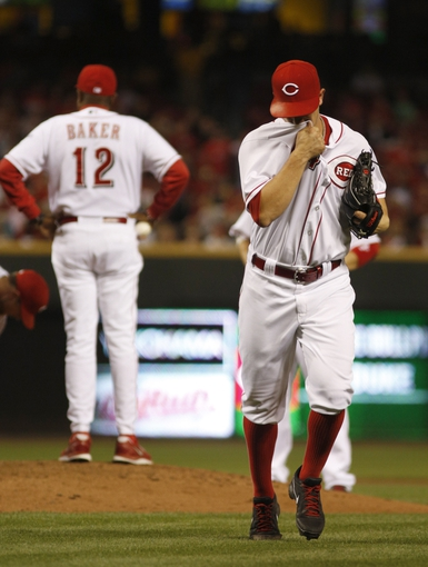 Sep 24, 2013; Cincinnati, OH, USA; Cincinnati Reds starting pitcher Mike Leake leaves the game as manager Dusty Baker waits at the mound during a game against the New York Mets at Great American Ball Park. Mandatory Credit: David Kohl-USA TODAY Sports