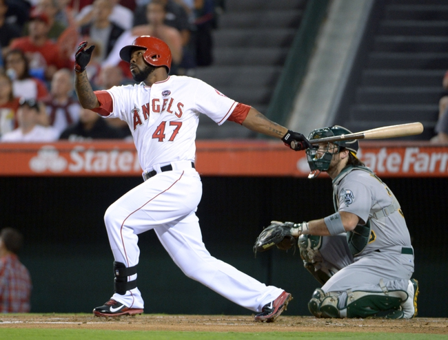 Sep 24, 2013; Anaheim, CA, USA; Los Angeles Angels second baseman Howie Kendrick (47) follows through on a solo home run in the first inning as Oakland Athletics catcher Derek Norris (36) watches at Angel Stadium of Anaheim. Mandatory Credit: Kirby Lee-USA TODAY Sports