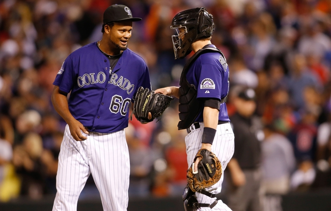 Sep 24, 2013; Denver, CO, USA; Colorado Rockies pitcher Manny Corpas (60) and catcher Jordan Pacheco (left) celebrate after the game against the Boston Red Sox at Coors Field. The Rockies won 8-3.  Mandatory Credit: Chris Humphreys-USA TODAY Sports
