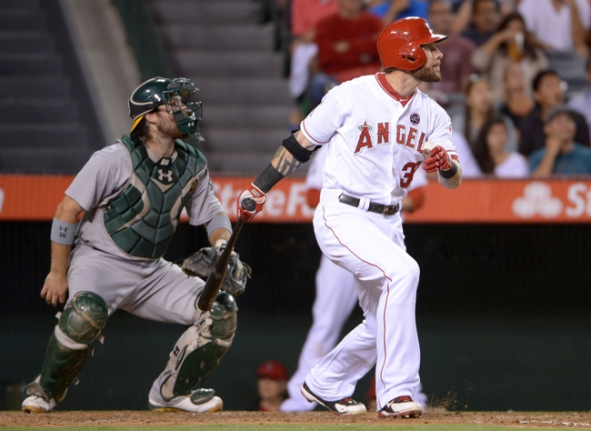 Sep 24, 2013; Anaheim, CA, USA; Los Angeles Angels center fielder Josh Hamilton (32) follows through on two run single in the third inning as Oakland Athletics catcher Derek Norris (36) watches at Angel Stadium of Anaheim. Mandatory Credit: Kirby Lee-USA TODAY Sports