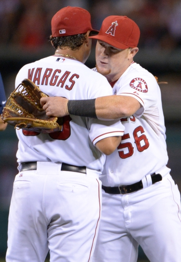 Sep 24, 2013; Anaheim, CA, USA; Los Angeles Angels pitcher Jason Vargas (56) and right fielder Kole Calhoun (56) embrace at the end of the game against the Oakland Athletics at Angel Stadium of Anaheim. The Angels defeated the Athletics 3-0. Mandatory Credit: Kirby Lee-USA TODAY Sports