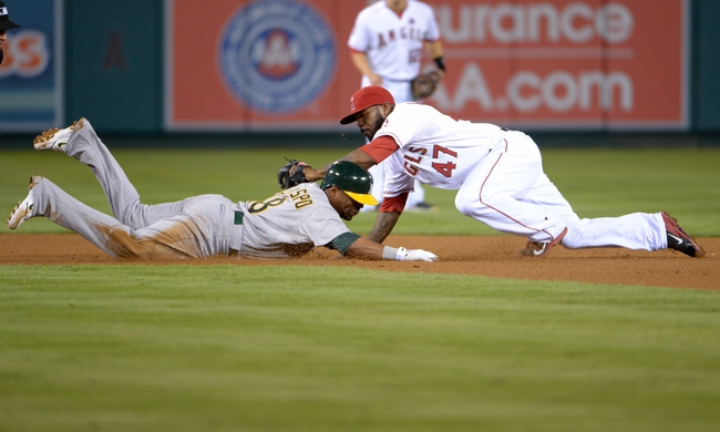 Sep 24, 2013; Anaheim, CA, USA; Oakland Athletics second baseman Alberto Callaspo (18) is tagged out by Los Angeles Angels second baseman Howie Kendrick (47) at second base in the eighth inning after trying to stretch a single into a double at Angel Stadium of Anaheim. The Angels defeated the Athletics 3-0. Mandatory Credit: Kirby Lee-USA TODAY Sports