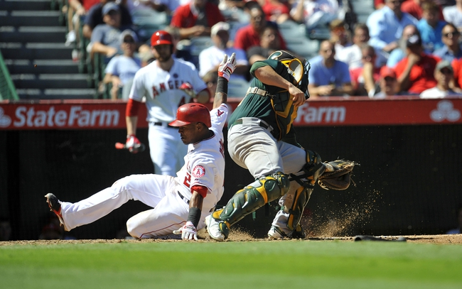 September 25, 2013; Anaheim, CA, USA; Los Angeles Angels shortstop Erick Aybar (2) slides past Oakland Athletics catcher Stephen Vogt (21) to score a run in the fourth inning at Angel Stadium of Anaheim. Mandatory Credit: Gary A. Vasquez-USA TODAY Sports