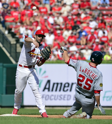 Sep 25, 2013; St. Louis, MO, USA; St. Louis Cardinals second baseman Matt Carpenter (13) turns a double play over Washington Nationals first baseman Adam LaRoche (25) at Busch Stadium. The Cardinals defeated the Nationals 4-1. Mandatory Credit: Scott Rovak-USA TODAY Sports