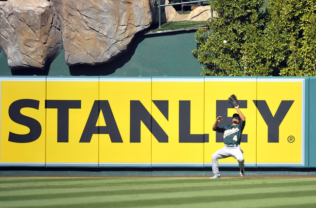 September 25, 2013; Anaheim, CA, USA; Oakland Athletics center fielder Coco Crisp (4) catches a fly ball in the eighth inning against the Los Angeles Angels at Angel Stadium of Anaheim. Mandatory Credit: Gary A. Vasquez-USA TODAY Sports