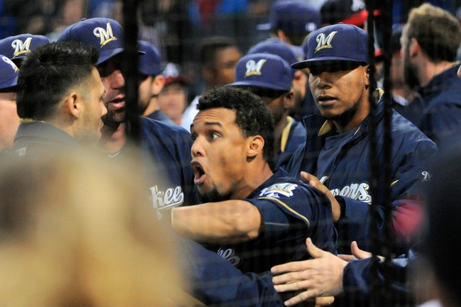 Sep 25, 2013; Atlanta, GA, USA; Milwaukee Brewers center fielder Carlos Gomez (27) is restrained by team mates while confronting  Atlanta Braves players after hitting a home run during the first inning at Turner Field. Mandatory Credit: Dale Zanine-USA TODAY Sports