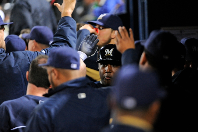 Sep 25, 2013; Atlanta, GA, USA; Milwaukee Brewers third baseman Yuniesky Betancourt (center) shakes hands with teammates in the dugout after scoring a run against the Atlanta Braves during the fourth inning at Turner Field. Mandatory Credit: Dale Zanine-USA TODAY Sports