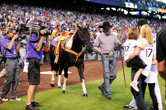 Sep 25, 2013; Denver, CO, USA; Colorado Rockies first baseman Todd Helton (right) receives a horse for retirement before the game against the Boston Red Sox at Coors Field. Mandatory Credit: Ron Chenoy-USA TODAY Sports