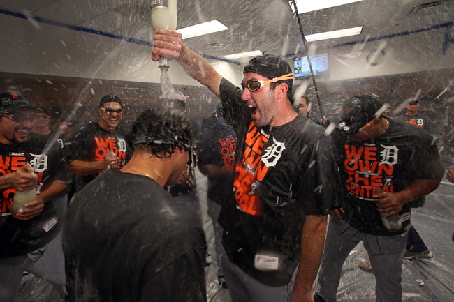 Sep 25, 2013; Minneapolis, MN, USA; Detroit Tigers starting pitcher Justin Verlander (35) drops champagne over a team mate after winning the Central Division Championship at Target Field. The Tigers won 1-0. Mandatory Credit: Jesse Johnson-USA TODAY Sports