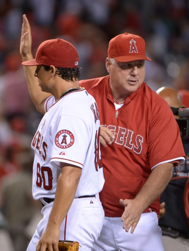 Sep 24, 2013; Anaheim, CA, USA; Los Angeles Angels pitcher Jason Vargas (56) is congratulated by manager Mike Scioscia (right) at the end of the game against the Oakland Athletics at Angel Stadium of Anaheim. The Angels defeated the Athletics 3-0. Mandatory Credit: Kirby Lee-USA TODAY Sports
