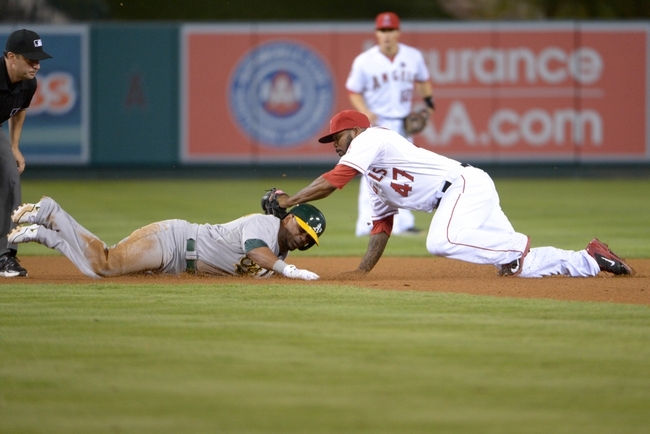 Sep 24, 2013; Anaheim, CA, USA; Oakland Athletics second baseman Alberto Callaspo (18) is tagged out by Los Angeles Angels second baseman Howie Kendrick (47) at second base in the eighth inning after trying to stretch a single into a double as second base umpire James Hoye (left) watches at Angel Stadium of Anaheim. The Angels defeated the Athletics 3-0. Mandatory Credit: Kirby Lee-USA TODAY Sports
