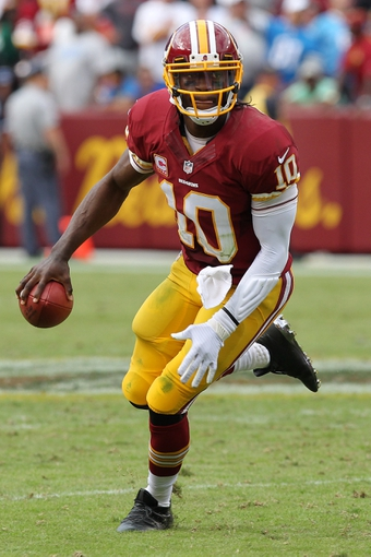 Sep 22, 2013; Landover, MD, USA; Washington Redskins quarterback Robert Griffin III (10) runs with the ball against the Detroit Lions at FedEx Field. Mandatory Credit: Geoff Burke-USA TODAY Sports
