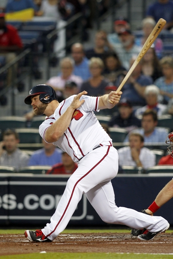 Sep 26, 2013; Atlanta, GA, USA; Atlanta Braves left fielder Evan Gattis (24) hits a RBI single against the Philadelphia Phillies in the first inning at Turner Field. Mandatory Credit: Brett Davis-USA TODAY Sports