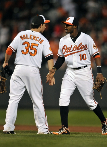 Sep 26, 2013; Baltimore, MD, USA; Baltimore Orioles teammates Danny Valencia (35) and Adam Jones (10) celebrate after a game against the Toronto Blue Jays at Oriole Park at Camden Yards. The Orioles defeated the Blue Jays 3-2. Mandatory Credit: Joy R. Absalon-USA TODAY Sports