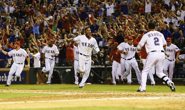 Sep 26, 2013; Arlington, TX, USA; Texas Rangers shortstop Elvis Andrus (middle) and teammates celebrate the walk off home run hit by Texas Rangers second baseman Jurickson Profar (not pictured) during the ninth inning against the Los Angeles Angels at Rangers Ballpark in Arlington. Mandatory Credit: Kevin Jairaj-USA TODAY Sports