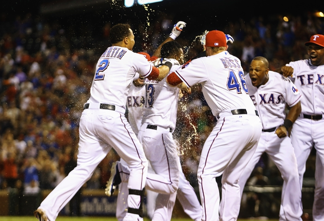 Sep 26, 2013; Arlington, TX, USA; Texas Rangers second baseman Jurickson Profar (middle) hits a walk off home run and is greeted by teammates on his way to home plate during the ninth inning against the Los Angeles Angels at Rangers Ballpark in Arlington. Mandatory Credit: Kevin Jairaj-USA TODAY Sports