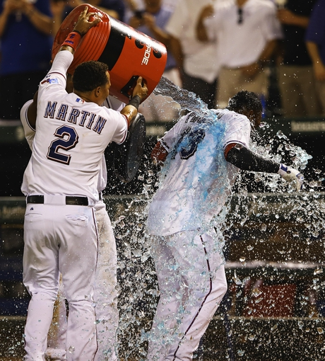 Sep 26, 2013; Arlington, TX, USA; Texas Rangers second baseman Jurickson Profar (13) gets a gatorade bath by  center fielder Leonys Martin (2) after hitting a walk off home run during the ninth inning against the Los Angeles Angels at Rangers Ballpark in Arlington. Mandatory Credit: Kevin Jairaj-USA TODAY Sports