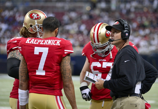 Sep 26, 2013; St. Louis, MO, USA; San Francisco 49ers head coach Jim Harbaugh talks with quarterback Colin Kaepernick (7) during the second half against the St. Louis Rams at the Edward Jones Dome. The 49ers defeated the Rams 35-11. Mandatory Credit: Scott Rovak-USA TODAY Sports