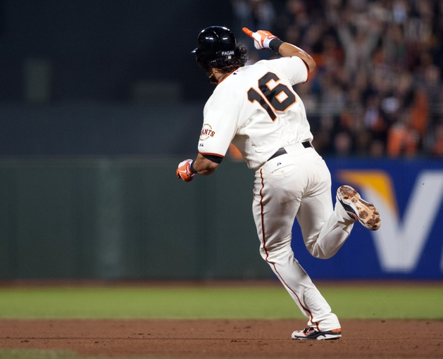Sep 26, 2013; San Francisco, CA, USA; San Francisco Giants center fielder Angel Pagan (16) raises his arm after hitting a home run during the eighth inning against the Los Angeles Dodgers at AT&T Park. The San Francisco Giants defeated the Los Angeles Dodgers 3-2. Mandatory Credit: Ed Szczepanski-USA TODAY Sports