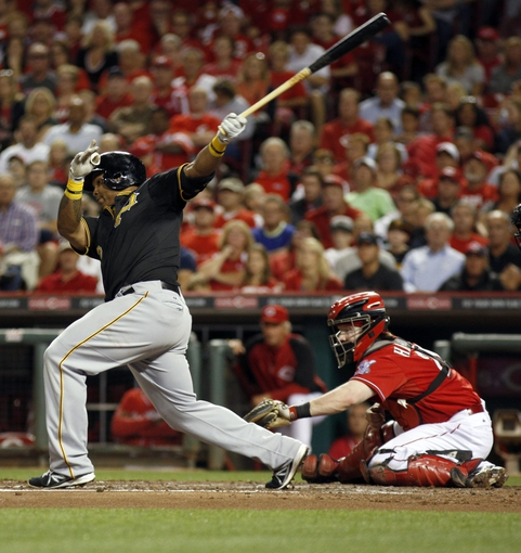 Sep 27, 2013; Cincinnati, OH, USA; Pittsburgh Pirates right fielder Marlon Byrd (left) hits single driving in two runs off Cincinnati Reds starting pitcher Homer Bailey (not pictured) in the third inning at Great American Ball Park. Reds catcher Ryan Hanigan is at right. Mandatory Credit: David Kohl-USA TODAY Sports