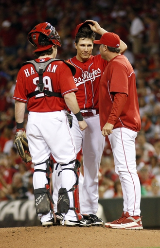 Sep 27, 2013; Cincinnati, OH, USA; Cincinnati Reds pitching coach Bryan Price (right) talks with starting pitcher Homer Bailey (center) as catcher Ryan Hanigan (left) listens in the third inning at Great American Ball Park. Mandatory Credit: David Kohl-USA TODAY Sports