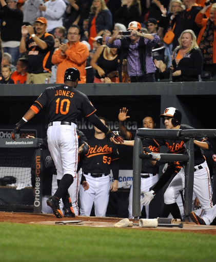 Sep 27, 2013; Baltimore, MD, USA; Baltimore Orioles center fielder Adam Jones (10) is congratulated by teammates after hitting a two-run home run in the third inning against the Boston Red Sox at Oriole Park at Camden Yards. Mandatory Credit: Joy R. Absalon-USA TODAY Sports