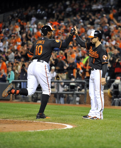Sep 27, 2013; Baltimore, MD, USA; Baltimore Orioles center fielder Adam Jones (10) is congratulated by Brian Roberts (1) after hitting a two-run home run in the third inning against the Boston Red Sox at Oriole Park at Camden Yards. Mandatory Credit: Joy R. Absalon-USA TODAY Sports