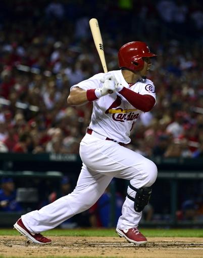 Sep 27, 2013; St. Louis, MO, USA; St. Louis Cardinals center fielder Jon Jay (19) hits an RBI single against the Chicago Cubs during the first inning at Busch Stadium. Mandatory Credit: Scott Rovak-USA TODAY Sports